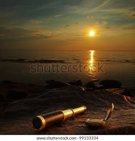 antique brass telescope and compass at sea coast stone - stock photo