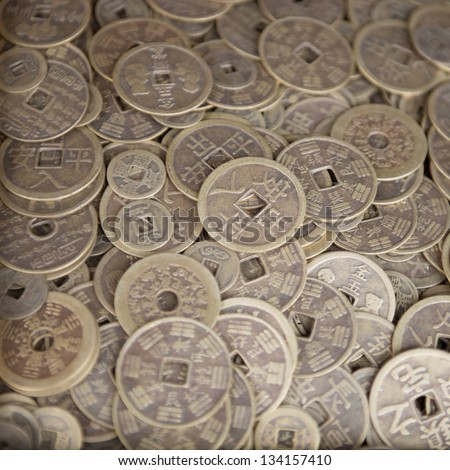 Antique bronze Chinese coins close-up background with selective focus on the middle - stock photo