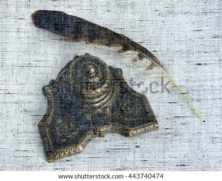 Antique Bronze inkpot with feather on white background with shadows - Photo made with canvas texture effect    - stock photo
