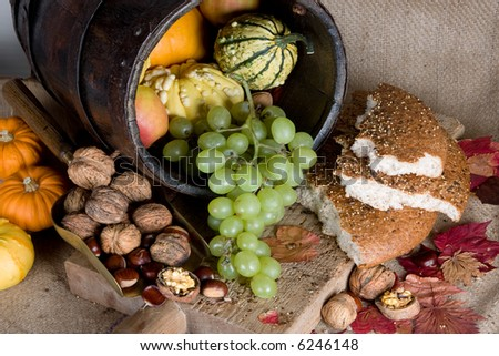 Antique bucket filled with autumn products, and traditional bread on a wooden board