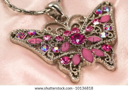 Antique butterfly necklace on pink silk