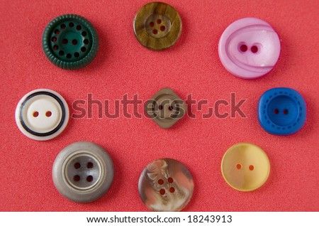 Antique buttons on red background - stock photo