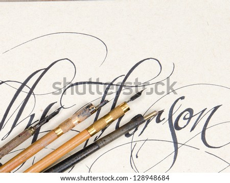 Antique calligraphy pens with fancy writing on textured paper. - stock photo