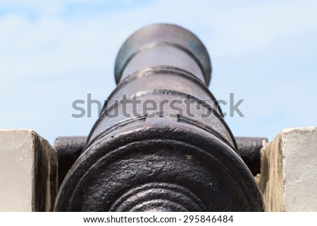 Antique cannon on the blue sky background - stock photo