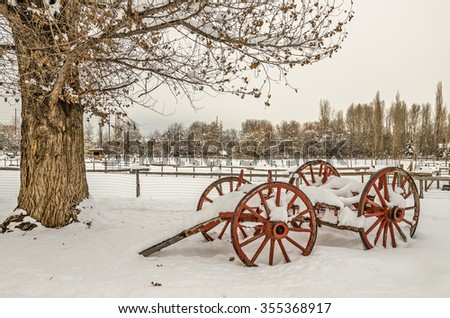 Antique cart covered with snow with wooden wheels that have been painted a red orange color sits next to a tree that hasn't yet lost all its leaves
