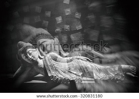 Antique carved wooden Buddha, reclining Buddha posture. selective focus. - stock photo