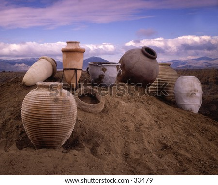 antique clay pots in a mound of sand - stock photo