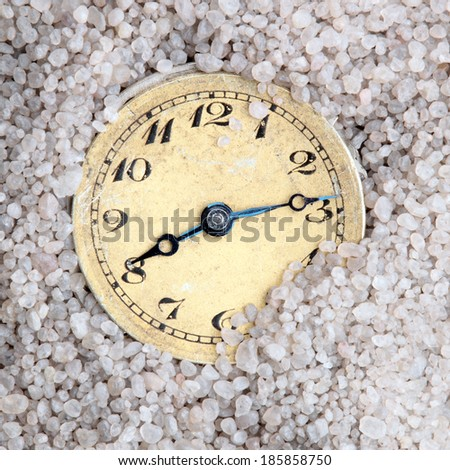 antique clock buried in sand - stock photo