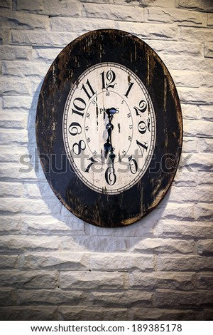 Antique clock on a building. Ancient white brick wall - stock photo