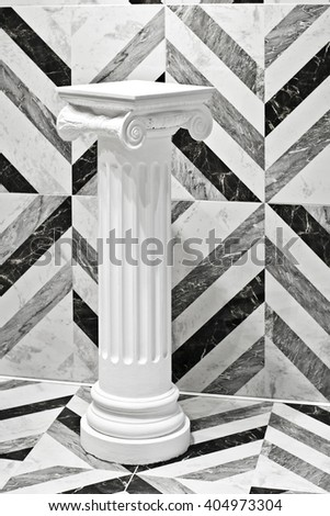 Antique column on the background black and white wall - stock photo