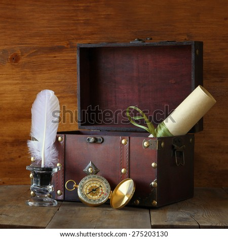 Antique compass, inkwell and old wooden chest on wooden table - stock photo