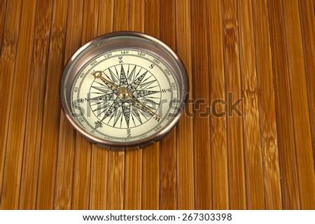 Antique compass on a brown wooden background. - stock photo