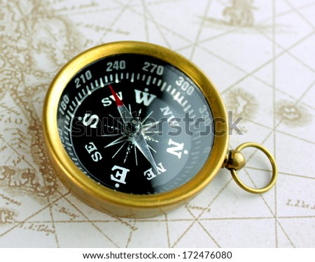Antique compass on map. Close up image. - stock photo