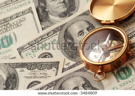Antique compass over 100 dollar bills background