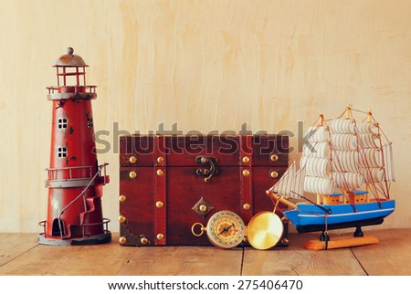 antique compass, vintage lighthouse, wooden boat and old chest  on wooden table - stock photo