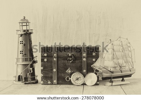 Antique compass, vintage lighthouse, wooden boat and old chest on wooden table. black and white style old photo - stock photo
