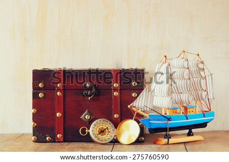 antique compass, wooden boat and old chest  on wooden table - stock photo