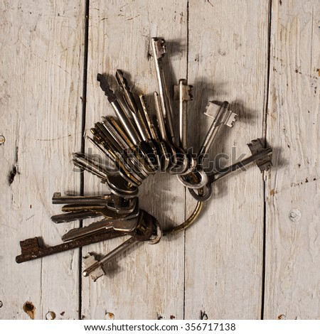 Antique copper keys on old wooden background - stock photo