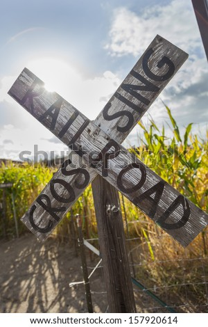 Antique Country Rail Road Crossing Sign Near a Corn Field in a Rustic Outdoor Setting.  - stock photo
