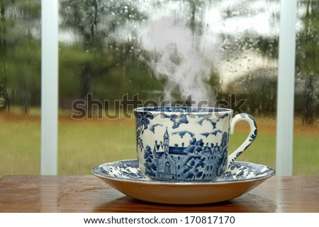 Antique Cup and Saucer with hot coffee by window on rainy day - stock photo