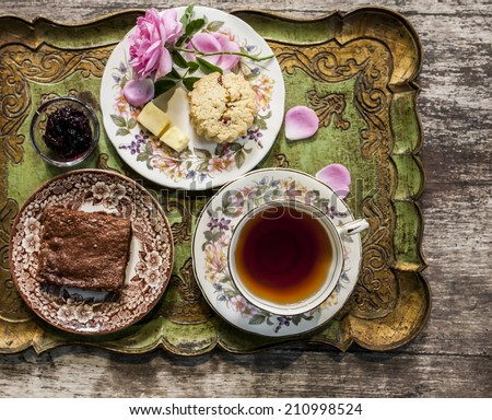 Antique cup full of tea with small cakes - stock photo