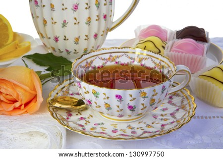 Antique cup full of tea with small cakes and in backbround isolated on white. - stock photo