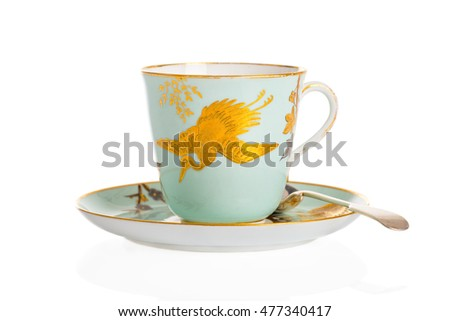 Antique cup, saucer and spoon on a white background