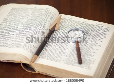 Antique dictionary with book knife and lens on it - stock photo