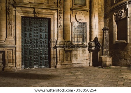 """Antique door and """"The pilgrim shadow"""" Famous landmark in the Santiago the Compostela Cathedral. Santiago de Compostela is one of the four holy places of Christianity. - stock photo"""