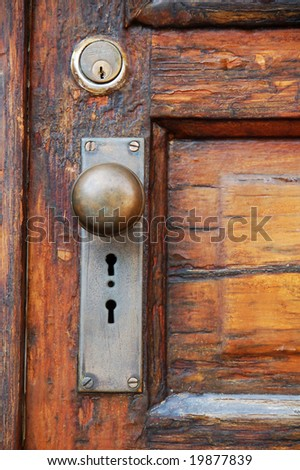 antique door knob on old wooden door with panels