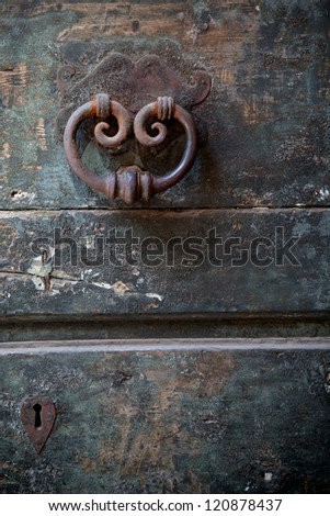 antique door-knocker on old door with keyhole