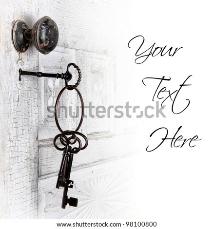 Antique door with keys in the lock isolated area for text - stock photo