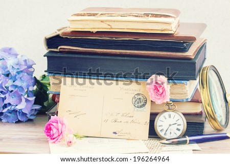 antique empty postcard with vintage books  on table - stock photo