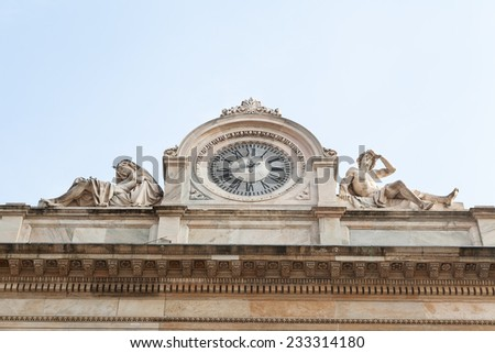 Antique fa?ade with clock and naked sculptures of man and woman - stock photo