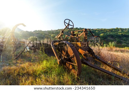 Antique Farm Equipment and Old hay rake at sunrise, Italy - stock photo