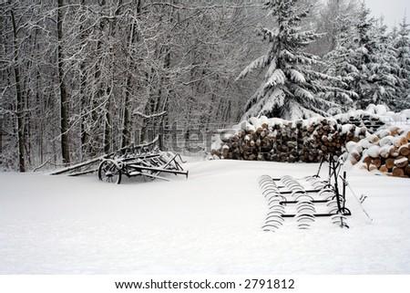 antique farm equipment in snow - stock photo