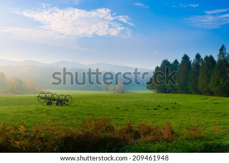 Antique farm implement in a farming landscape, Stowe Vermont, USA - stock photo