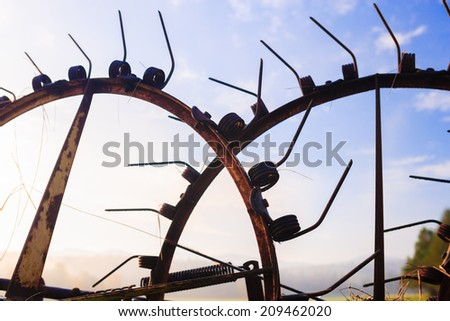Antique farm implements silhouetted against the blue sky, Stowe Vermont, USA - stock photo