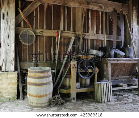 Antique farm tools on the floor and hanging on the wall of an old wood barn. - stock photo