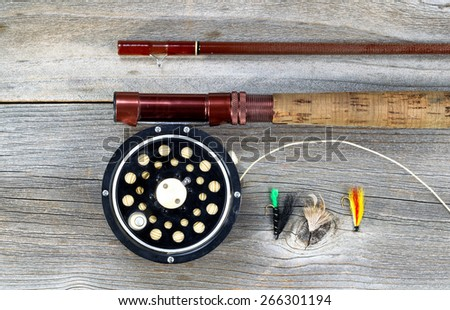 Antique fly fishing reel and rod on rustic wood. Layout in horizontal format. - stock photo