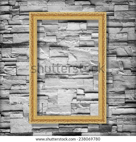 Antique gold frame on stone wall background ,gold picture frame on sandstone brick wall Surfaced background