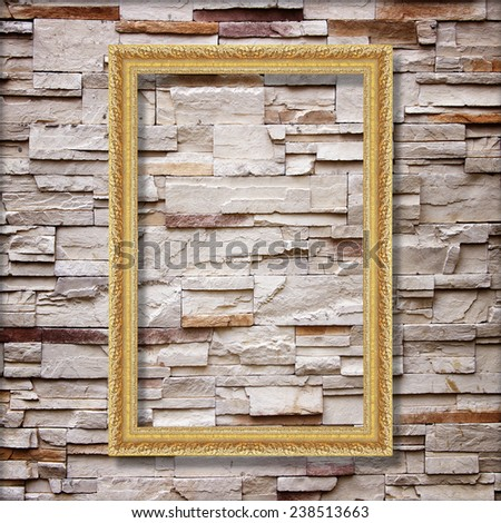 Antique gold frame on stone wall background ,goldr picture frame on sandstone brick wall Surfaced background