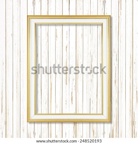 Antique gold frame on white wooden wall ;. Empty picture frame on white wooden wall.