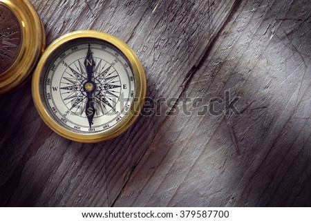 Antique golden compass on wood background concept for direction, travel, guidance or assistance - stock photo