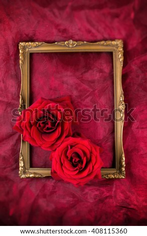 Antique golden picture frame on burgundy fabric, with red roses