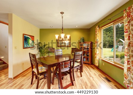 Antique green dining room interior with mahogany table set and chandelier. Hardwood floor and white ceiling. View of back yard with kids playground.