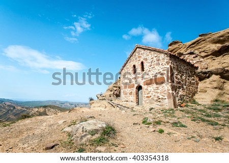 Antique historical chapel built in cliff in David Gareji monastery complex on Geargian-Azerbaijan border ridge. Colorful summertime vibrant outdoors horizontal image on blue cloudy sky background.