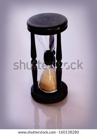 Antique hourglass. Isolated on a purple background - stock photo