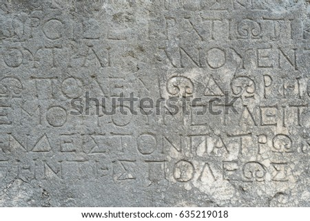 Antique inscription on a stone wall. Historic landmark in the old, ruined city of Faselis, Turkey
