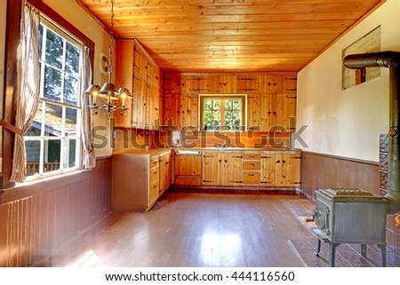 Antique kitchen room interior with old iron stove, wood ceiling and plank trim wall.